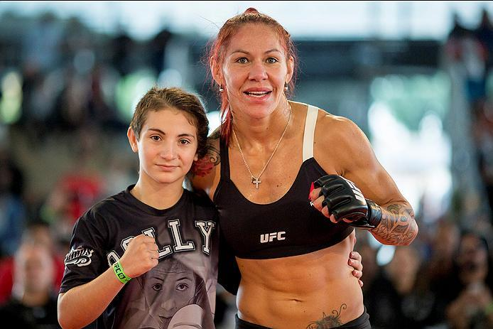 """RIO DE JANEIRO, BRAZIL - MAY 11: Catchweight Cris """"Cyborg Justino of Brazil poses for a photo with a fan during an open training session at Arena da Baixada stadium on May 11, 2016 in Curitiba, Brazil. (Photo by Buda Mendes/Zuffa LLC/Zuffa LLC via Getty I"""