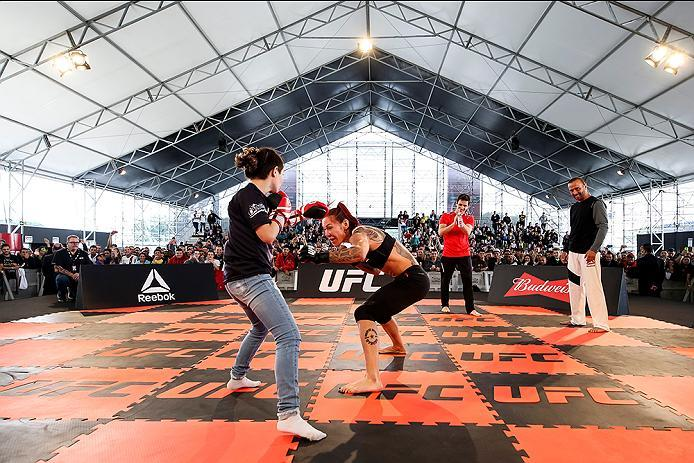 """RIO DE JANEIRO, BRAZIL - MAY 11: Catchweight Cris """"Cyborg Justino of Brazil holds with a fan an open training session at Arena da Baixada stadium on May 11, 2016 in Curitiba, Brazil. (Photo by Buda Mendes/Zuffa LLC/Zuffa LLC via Getty Images) ***Local Cap"""