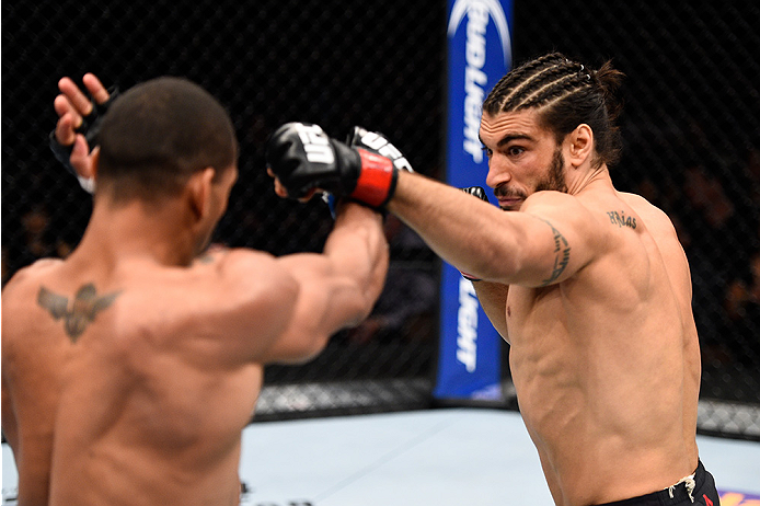 LAS VEGAS, NEVADA - DECEMBER 10:  (R) Elias Theodorou punches Thiago Santos in their middleweight bout during the UFC Fight Night event at The Chelsea at the Cosmopolitan of Las Vegas on December 10, 2015 in Las Vegas, Nevada.  (Photo by Jeff Bottari/Zuff