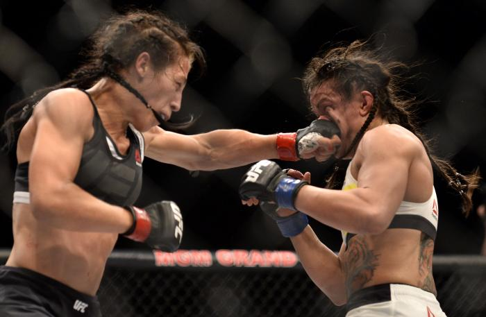 LAS VEGAS, NV - JULY 08:  (L-R) Joanna Jedrzejczyk of Poland punches Claudia Gadelha of Brazil in their women's strawweight championship bout during The Ultimate Fighter Finale event at MGM Grand Garden Arena on July 8, 2016 in Las Vegas, Nevada.  (Photo