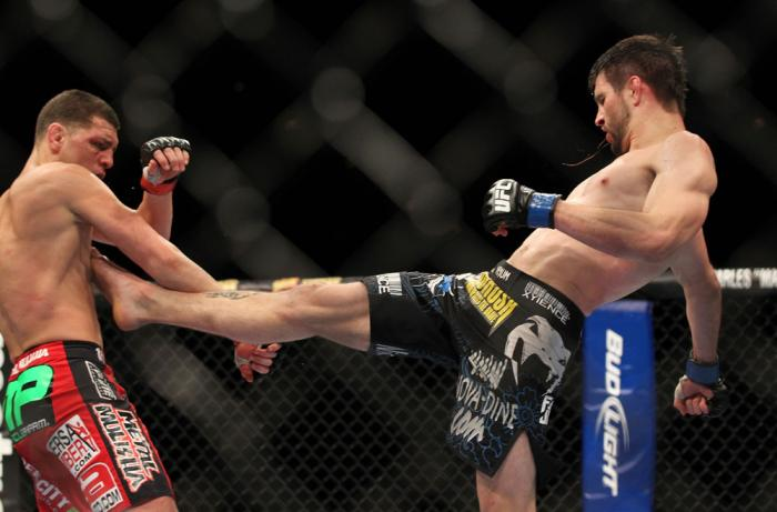 LAS VEGAS - FEBRUARY 04:  (R-L) Carlos Condit kicks Nick Diaz during the UFC 143 event at Mandalay Bay Events Center on February 4, 2012 in Las Vegas, Nevada.  (Photo by Josh Hedges/Zuffa LLC/Zuffa LLC via Getty Images) *** Local Caption *** Carlos Condit