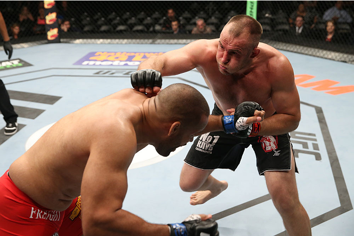 SAN ANTONIO, TX - JUNE 28:  (R-L) Oleksiy Oliynyk punches Anthony Hamilton in their heavyweight bout at the AT&T Center on June 28, 2014 in San Antonio, Texas. (Photo by Ed Mulholland/Zuffa LLC/Zuffa LLC via Getty Images)