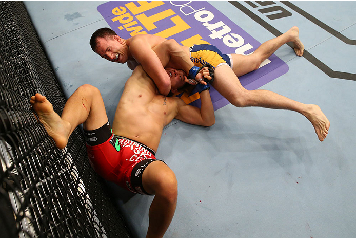 SAN ANTONIO, TX - JUNE 28:  Joe Ellenberger (top) attempts to submit James Moontasri in their lightweight bout at the AT&T Center on June 28, 2014 in San Antonio, Texas. (Photo by Ed Mulholland/Zuffa LLC/Zuffa LLC via Getty Images)