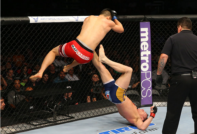 SAN ANTONIO, TX - JUNE 28:  James Moontasri (red shorts) delivers an elbow drop to Joe Ellenberger (blue shorts) in their lightweight bout at the AT&T Center on June 28, 2014 in San Antonio, Texas. (Photo by Ed Mulholland/Zuffa LLC/Zuffa LLC via Getty Ima