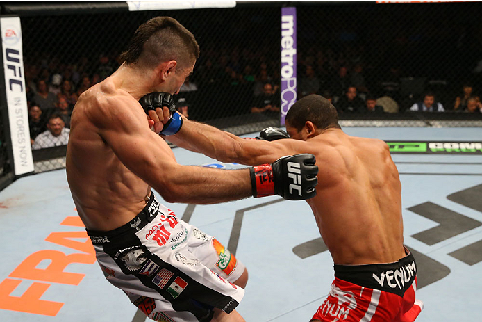SAN ANTONIO, TX - JUNE 28:  (R-L) Hacran Dias punches Ricardo Lamas in their featherweight bout at the AT&T Center on June 28, 2014 in San Antonio, Texas. (Photo by Ed Mulholland/Zuffa LLC/Zuffa LLC via Getty Images)