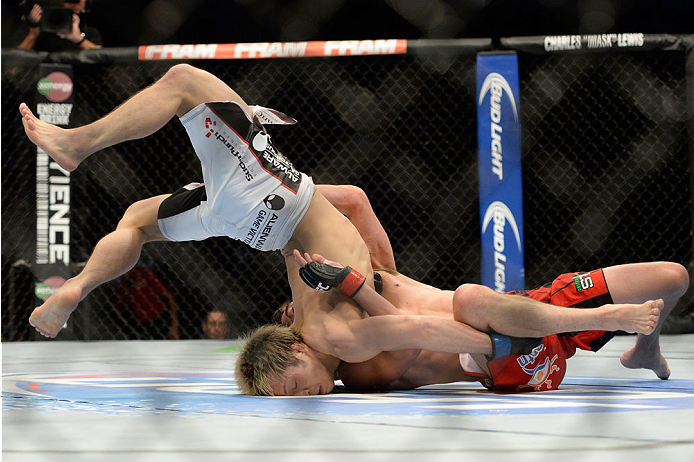 VANCOUVER, BC - JUNE 14:  (L-R) Michinori Tanaka is flipped over by Roland Delorme during the UFC 174 event at Rogers Arena on June 14, 2014 in Vancouver, British Columbia, Canada. (Photo by Jeff Bottari/Zuffa LLC/Zuffa LLC via Getty Images)