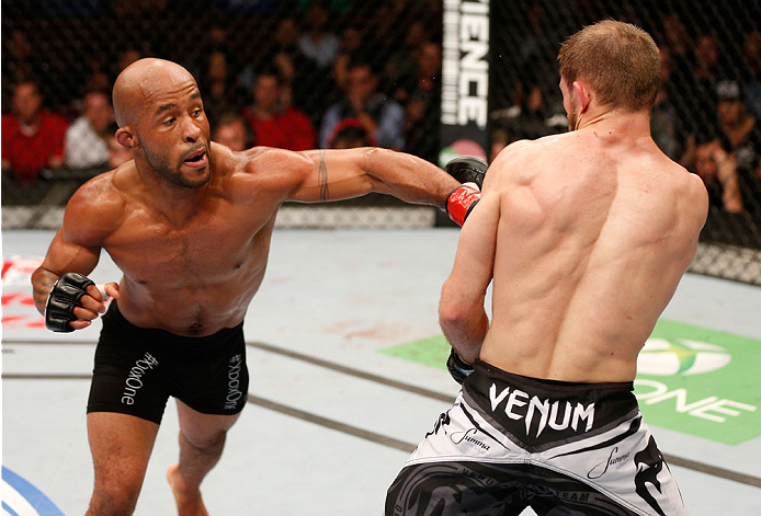 "VANCOUVER, BC - JUNE 14:  (L-R) Demetrious ""Mighty Mouse"" Johnson delivers a punch against Ali Bagautinov in their UFC flyweight championship bout at Rogers Arena on June 14, 2014 in Vancouver, Canada.  (Photo by Josh Hedges/Zuffa LLC/Zuffa LLC via Getty"