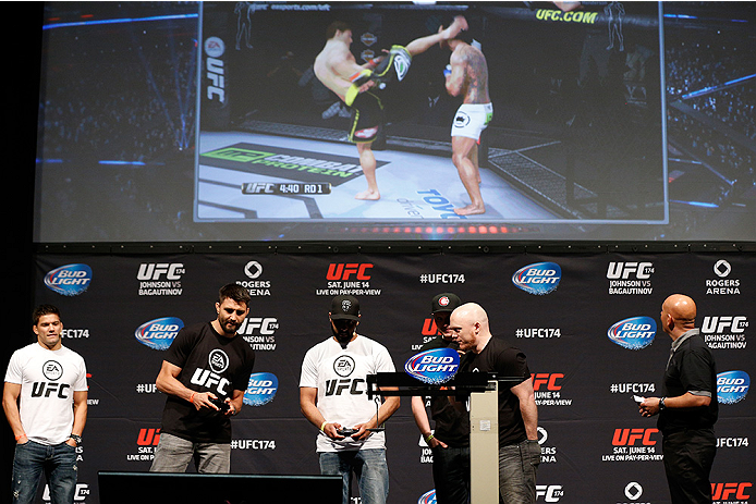 VANCOUVER, BC - JUNE 13:  Carlos Condit battles against a fan during a demo of the new EA Sports UFC videogame before the UFC 174 weigh-in at Rogers Arena on June 13, 2014 in Vancouver, Canada.  (Photo by Josh Hedges/Zuffa LLC/Zuffa LLC via Getty Images)