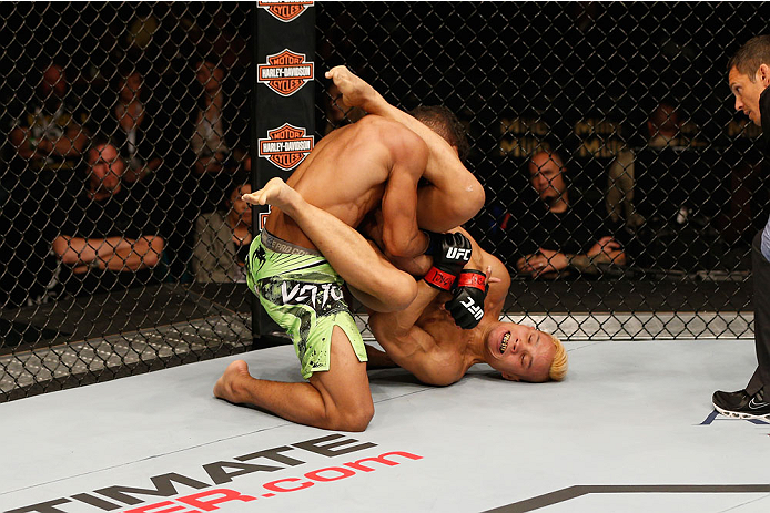 LAS VEGAS, NV - SEPTEMBER 27:  (R-L) Jon Tuck attempts an arm bar on Kevin Lee in their lightweight fight during the UFC 178 event inside the MGM Grand Garden Arena on September 27, 2014 in Las Vegas, Nevada.  (Photo by Josh Hedges/Zuffa LLC/Zuffa LLC via
