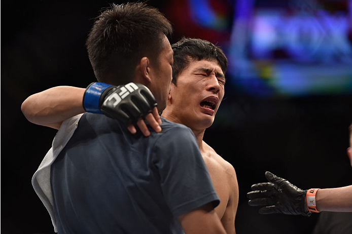 LAS VEGAS, NV - SEPTEMBER 27:  Takeya Mizugaki reacts after his TKO loss from Dominick Cruz in their bantamweight fight during the UFC 178 event inside the MGM Grand Garden Arena on September 27, 2014 in Las Vegas, Nevada.  (Photo by Jeff Bottari/Zuffa LL