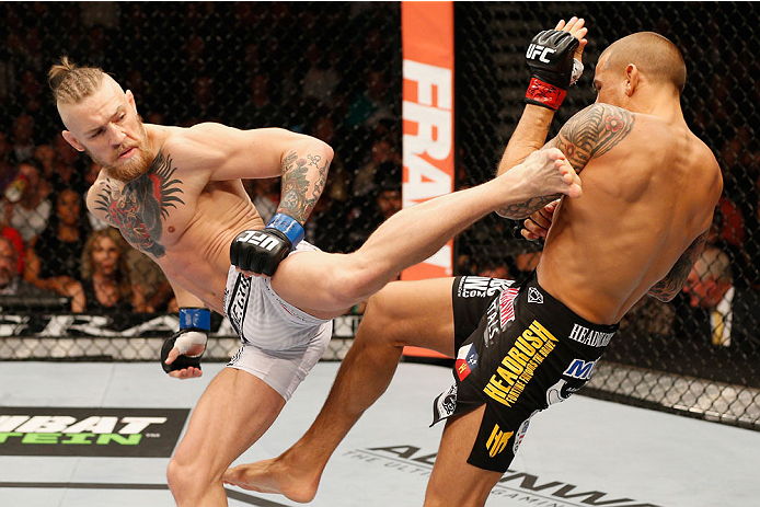 LAS VEGAS, NV - SEPTEMBER 27:  (L-R) Conor McGregor kicks Dustin Poirier in their featherweight fight during the UFC 178 event inside the MGM Grand Garden Arena on September 27, 2014 in Las Vegas, Nevada.  (Photo by Josh Hedges/Zuffa LLC/Zuffa LLC via Get