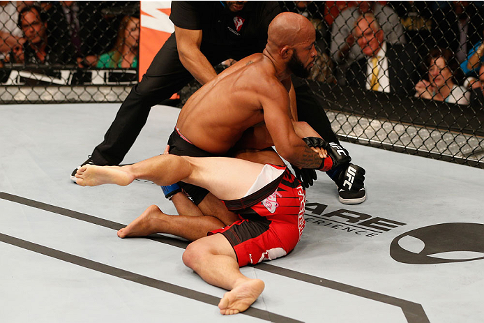 LAS VEGAS, NV - SEPTEMBER 27:  UFC Flyweight champion Demetrious Johnson submits Chris Cariaso in their flyweight championship fight during the UFC 178 event inside the MGM Grand Garden Arena on September 27, 2014 in Las Vegas, Nevada.  (Photo by Josh Hed
