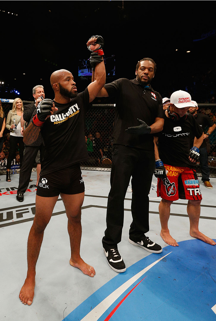 LAS VEGAS, NV - SEPTEMBER 27:  (L-R)UFC Flyweight champion Demetrious Johnson celebrates after his win over Chris Cariaso after their flyweight championship fight during the UFC 178 event inside the MGM Grand Garden Arena on September 27, 2014 in Las Vega