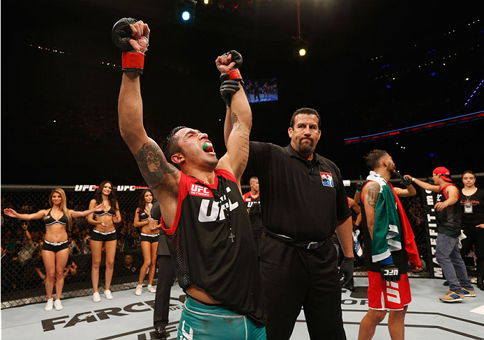 MEXICO CITY, MEXICO - NOVEMBER 15:  (L-R) Alejandro Perez celebrates his victory over Jose Quinonez in their bantamweight bout during the UFC 180 event at Arena Ciudad de Mexico on November 15, 2014 in Mexico City, Mexico.  (Photo by Josh Hedges/Zuffa LLC