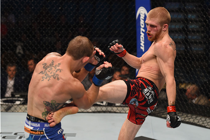 LAS VEGAS, NV - MAY 23:  (R-L) Justin Scoggins kicks Joshua Sampo in their flyweight bout during the UFC 187 event at the MGM Grand Garden Arena on May 23, 2015 in Las Vegas, Nevada.  (Photo by Josh Hedges/Zuffa LLC/Zuffa LLC via Getty Images)