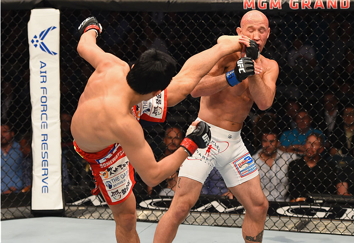 LAS VEGAS, NV - MAY 23:  (L-R) Dong Hyun Kim kicks Josh Burkman in their welterweight bout during the UFC 187 event at the MGM Grand Garden Arena on May 23, 2015 in Las Vegas, Nevada.  (Photo by Josh Hedges/Zuffa LLC/Zuffa LLC via Getty Images)