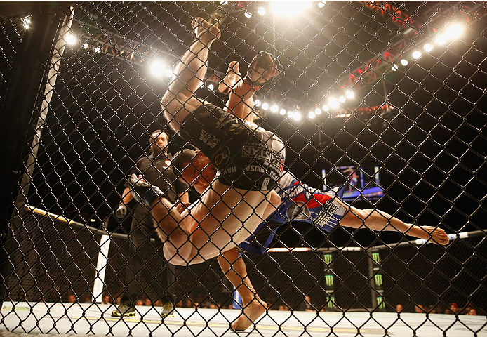 LAS VEGAS, NV - MAY 23:  John Dodson (blue shorts) takes down Zach Makovsky in their flyweight bout during the UFC 187 event at the MGM Grand Garden Arena on May 23, 2015 in Las Vegas, Nevada.  (Photo by Christian Petersen/Zuffa LLC/Zuffa LLC via Getty Im