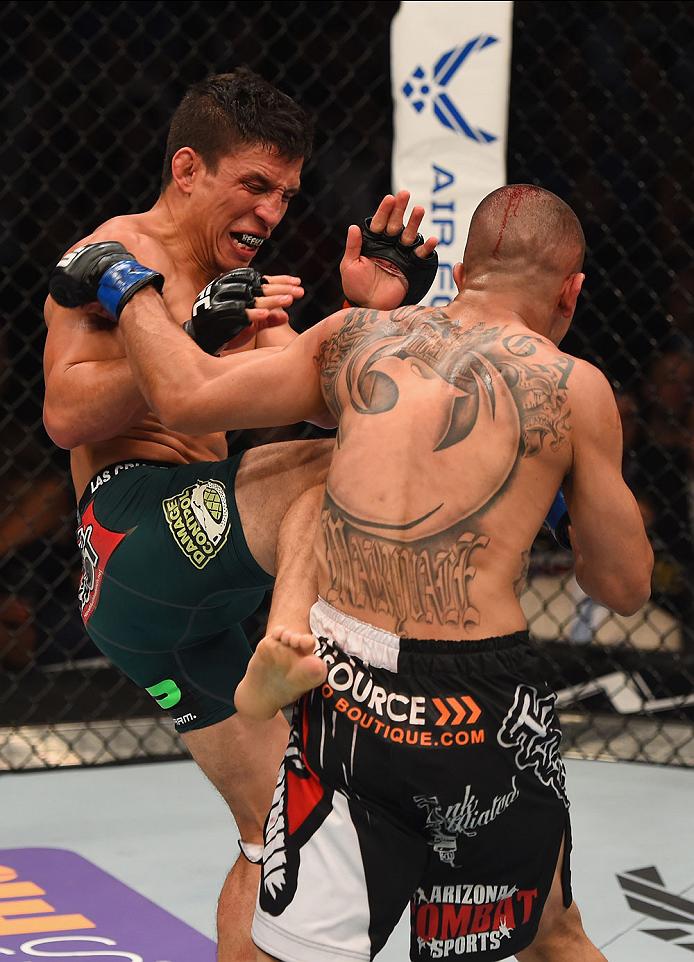 LAS VEGAS, NV - MAY 23:  (L-R) Joseph Benavidez kicks John Moraga in their flyweight bout during the UFC 187 event at the MGM Grand Garden Arena on May 23, 2015 in Las Vegas, Nevada.  (Photo by Josh Hedges/Zuffa LLC/Zuffa LLC via Getty Images)