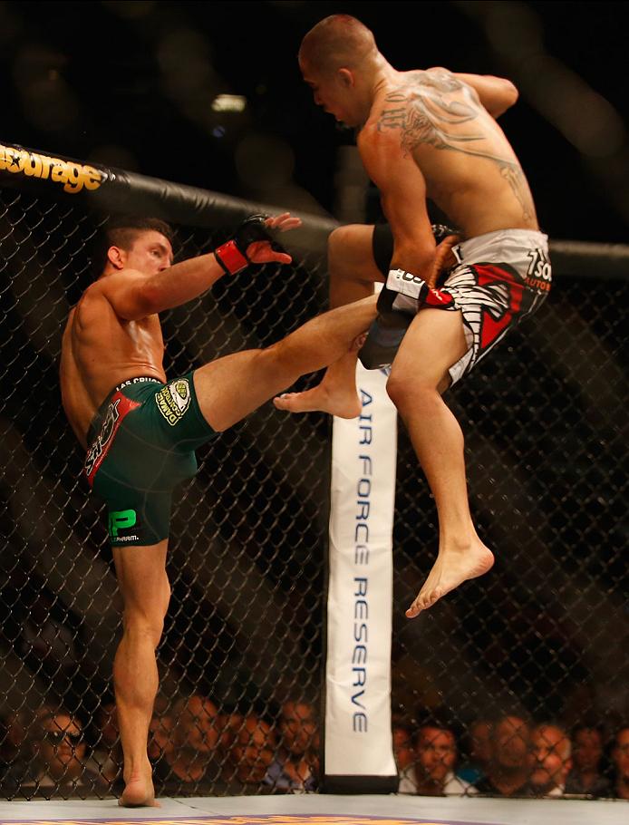 LAS VEGAS, NV - MAY 23:  (L-R) Joseph Benavidez kicks John Moraga in their flyweight bout during the UFC 187 event at the MGM Grand Garden Arena on May 23, 2015 in Las Vegas, Nevada.  (Photo by Christian Petersen/Zuffa LLC/Zuffa LLC via Getty Images)