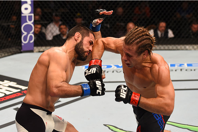 LAS VEGAS, NV - DECEMBER 12: (R-L) Urijah Faber punches Frankie Saenz in their bantamweight bout during the UFC 194 event inside MGM Grand Garden Arena on December 12, 2015 in Las Vegas, Nevada.  (Photo by Josh Hedges/Zuffa LLC/Zuffa LLC via Getty Images)