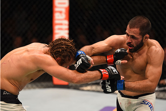 LAS VEGAS, NV - DECEMBER 12: (R-L) Frankie Saenz punches Urijah Faber in their bantamweight bout during the UFC 194 event inside MGM Grand Garden Arena on December 12, 2015 in Las Vegas, Nevada.  (Photo by Josh Hedges/Zuffa LLC/Zuffa LLC via Getty Images)
