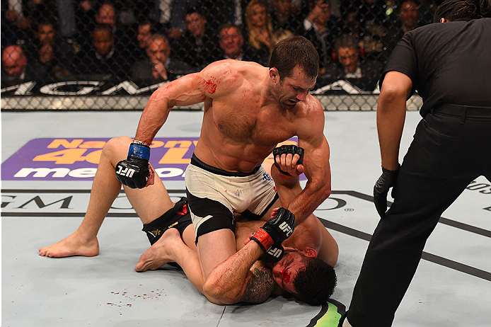 LAS VEGAS, NV - DECEMBER 12:  Luke Rockhold (top) punches Chris Weidman in their UFC middleweight championship bout during the UFC 194 event inside MGM Grand Garden Arena on December 12, 2015 in Las Vegas, Nevada.  (Photo by Josh Hedges/Zuffa LLC/Zuffa LL