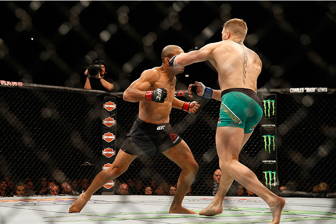 LAS VEGAS, NV - DECEMBER 12: (R-L) Conor McGregor of Ireland punches Jose Aldo of Brazil in their UFC welterweight championship bout during the UFC 194 event inside MGM Grand Garden Arena on December 12, 2015 in Las Vegas, Nevada.  (Photo by Christian Pet