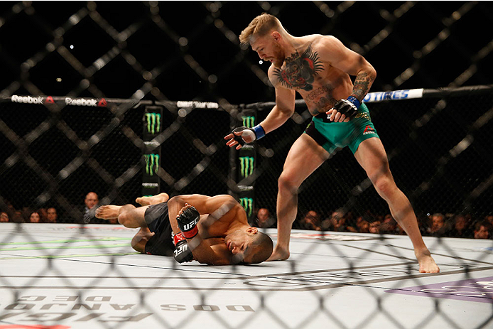 LAS VEGAS, NV - DECEMBER 12:  (R-L) Conor McGregor of Ireland punches Jose Aldo of Brazil in their UFC featherweight championship bout during the UFC 194 event inside MGM Grand Garden Arena on December 12, 2015 in Las Vegas, Nevada.  (Photo by Christian P