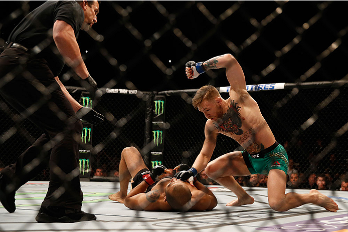 LAS VEGAS, NV - DECEMBER 12:  Conor McGregor of Ireland (top) punches Jose Aldo of Brazil in their UFC featherweight championship bout during the UFC 194 event inside MGM Grand Garden Arena on December 12, 2015 in Las Vegas, Nevada.  (Photo by Christian P