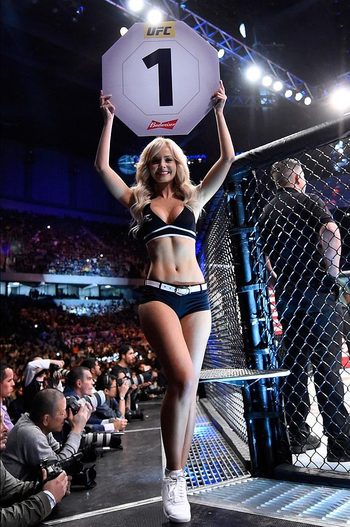 CURITIBA, BRAZIL - MAY 14:  UFC Octagon Girl Jhenny Andrade signals the start of round one between John Lineker of Brazil and Rob Font in their bantamweight bout during the UFC 198 event at Arena da Baixada stadium on May 14, 2016 in Curitiba, Parana, Bra