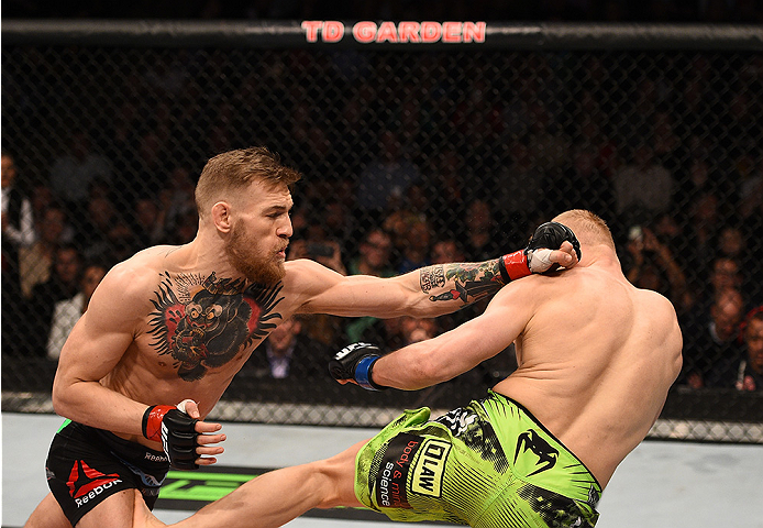 BOSTON, MA - JANUARY 18:  (L-R) Conor McGregor of Ireland punches Dennis Siver of Germany in their featherweight fight during the UFC Fight Night event at the TD Garden on January 18, 2015 in Boston, Massachusetts. (Photo by Jeff Bottari/Zuffa LLC/Zuffa L
