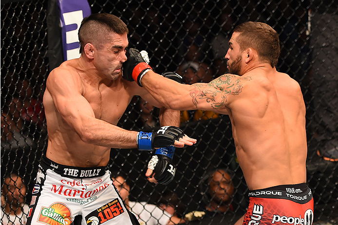 FAIRFAX, VA - APRIL 04:  (EDITOR'S NOTE: Alternative crop for #468617858) (R-L) Chad Mendes punches Ricardo Lamas in their featherweight fight during the UFC Fight Night event at the Patriot Center on April 4, 2015 in Fairfax, Virginia. (Photo by Josh Hed