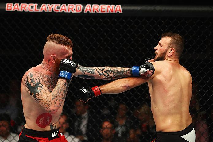 HAMBURG, GERMANY - SEPTEMBER 03:  Jim Wallhead (L) of England punches Jessin Ayari (R) of Germany compete in their Welterweight Bout during the UFC Fight Night held at Barclaycard Arena on September 3, 2016 in Hamburg, Germany.  (Photo by Dean Mouhtaropou