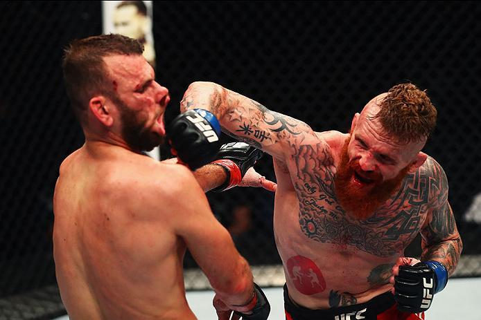 HAMBURG, GERMANY - SEPTEMBER 03:  Jim Wallhead (R) of England punches Jessin Ayari(L) of Germany compete in their Welterweight Bout during the UFC Fight Night held at Barclaycard Arena on September 3, 2016 in Hamburg, Germany.  (Photo by Dean Mouhtaropoul