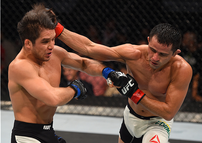 MONTERREY, MEXICO - NOVEMBER 21:  (R-L) Jussier Formiga of Brazil punches Henry Cejudo of the United States in their flyweight bout during the UFC Fight Night event at Arena Monterrey on November 21, 2015 in Monterrey, Mexico.  (Photo by Jeff Bottari/Zuff