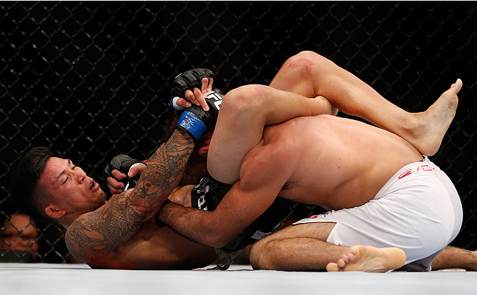SINGAPORE - JANUARY 04:  (L-R) Russell Doane secures a triangle choke submission against Leandro Issa in their bantamweight bout during the UFC Fight Night event at the Marina Bay Sands Resort on January 4, 2014 in Singapore. (Photo by Josh Hedges/Zuffa L