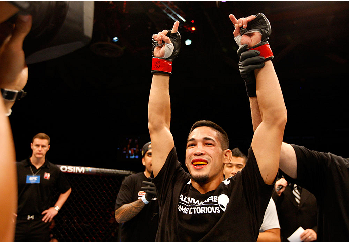 SINGAPORE - JANUARY 04:  Dustin Kimura celebrates his win over Jon Delos Reyes in their bantamweight bout during the UFC Fight Night event at the Marina Bay Sands Resort on January 4, 2014 in Singapore. (Photo by Mitch Viquez/Zuffa LLC/Zuffa LLC via Getty