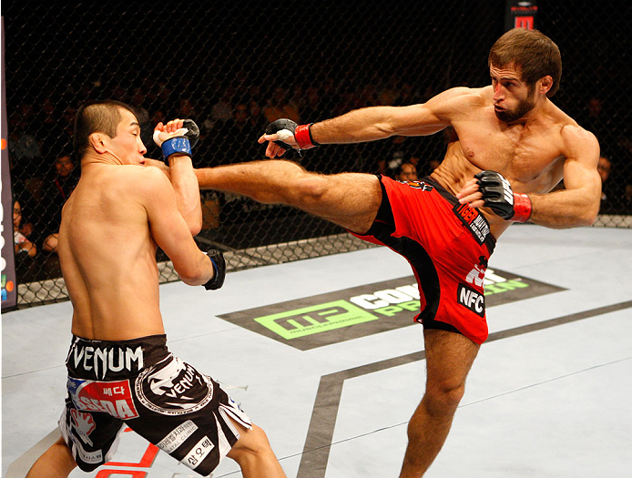 SINGAPORE - JANUARY 04:  Mairbek Taisumov goes for a kick on Bang Tae Hyun in their lightweight bout during the UFC Fight Night event at the Marina Bay Sands Resort on January 4, 2014 in Singapore. (Photo by Mitch Viquez/Zuffa LLC/Zuffa LLC via Getty Imag