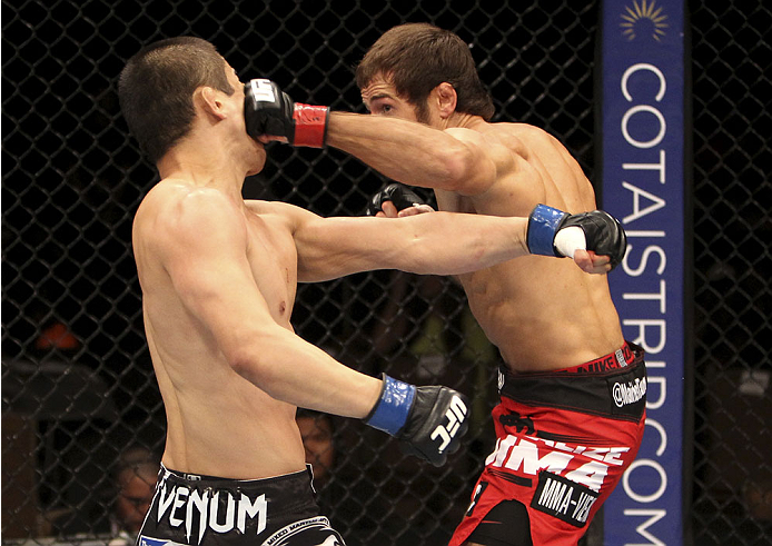 SINGAPORE - JANUARY 04:  Mairbek Taisumov lands a bunch on Bang Tae Hyun in their lightweight bout during the UFC Fight Night event at the Marina Bay Sands Resort on January 4, 2014 in Singapore. (Photo by Mitch Viquez/Zuffa LLC/Zuffa LLC via Getty Images