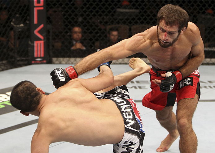 SINGAPORE - JANUARY 04:  Mairbek Taisumov goes for a punch on Bang Tae Hyun in their lightweight bout during the UFC Fight Night event at the Marina Bay Sands Resort on January 4, 2014 in Singapore. (Photo by Mitch Viquez/Zuffa LLC/Zuffa LLC via Getty Ima