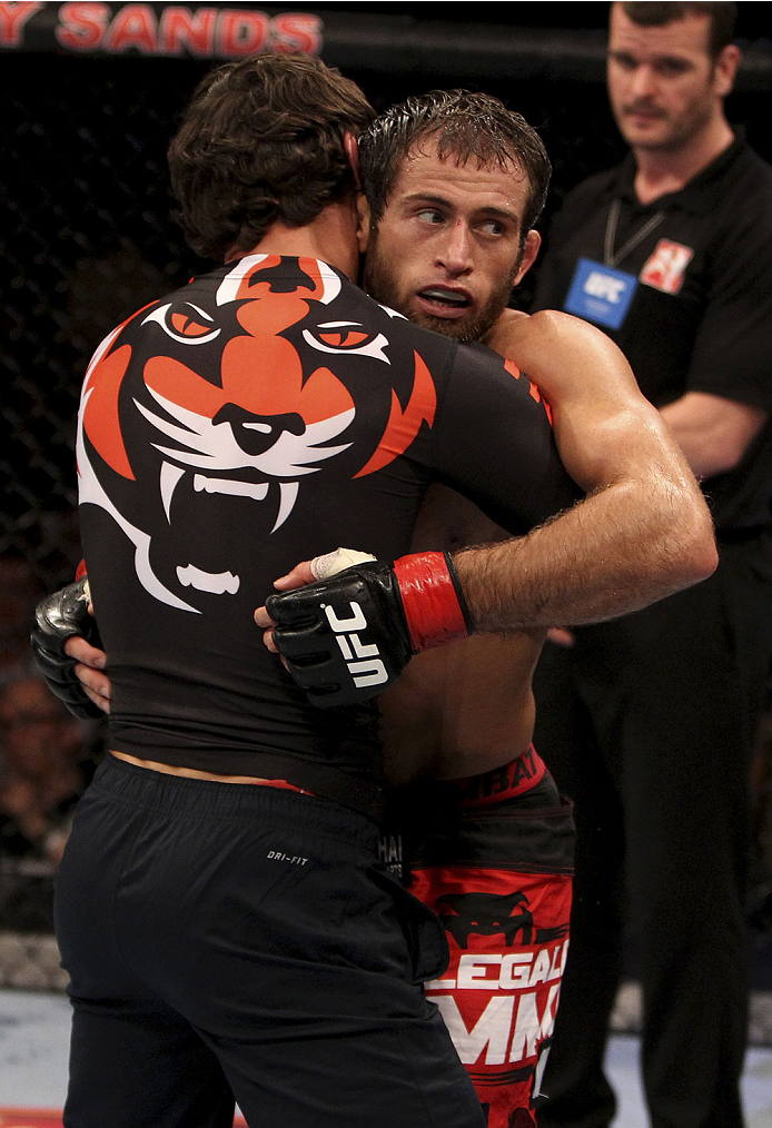 SINGAPORE - JANUARY 04:  Mairbek Taisumov is given a hug after his win  over Bang Tae Hyun in their lightweight bout during the UFC Fight Night event at the Marina Bay Sands Resort on January 4, 2014 in Singapore. (Photo by Mitch Viquez/Zuffa LLC/Zuffa LL