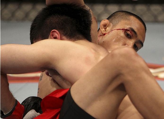 SINGAPORE - JANUARY 04:  David Galera suffers a little blood from his eye against Royston Wee in their bantamweight bout during the UFC Fight Night event at the Marina Bay Sands Resort on January 4, 2014 in Singapore. (Photo by Mitch Viquez/Zuffa LLC/Zuff