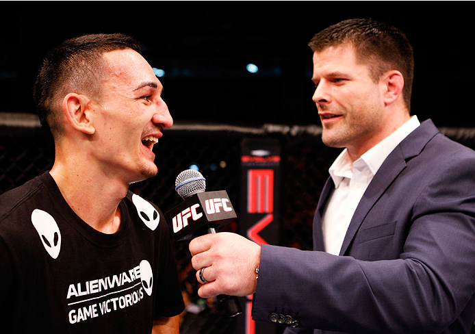 SINGAPORE - JANUARY 04:  (L-R) Max Holloway has a laugh with Brian Stann after his win over Will Chope in their featherweight bout during the UFC Fight Night event at the Marina Bay Sands Resort on January 4, 2014 in Singapore. (Photo by Mitch Viquez/Zuff