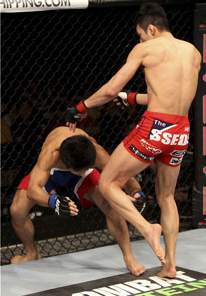 SINGAPORE - JANUARY 04:  Kang Kyung Ho goes for a knee on Shunichi Shimizu in their bantamweight bout during the UFC Fight Night event at the Marina Bay Sands Resort on January 4, 2014 in Singapore. (Photo by Mitch Viquez/Zuffa LLC/Zuffa LLC via Getty Ima