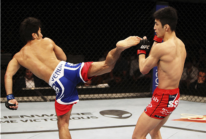 SINGAPORE - JANUARY 04: Shunichi Shimizu goes for a spinning back kick onKang Kyung Ho in their bantamweight bout during the UFC Fight Night event at the Marina Bay Sands Resort on January 4, 2014 in Singapore. (Photo by Mitch Viquez/Zuffa LLC/Zuffa LLC v