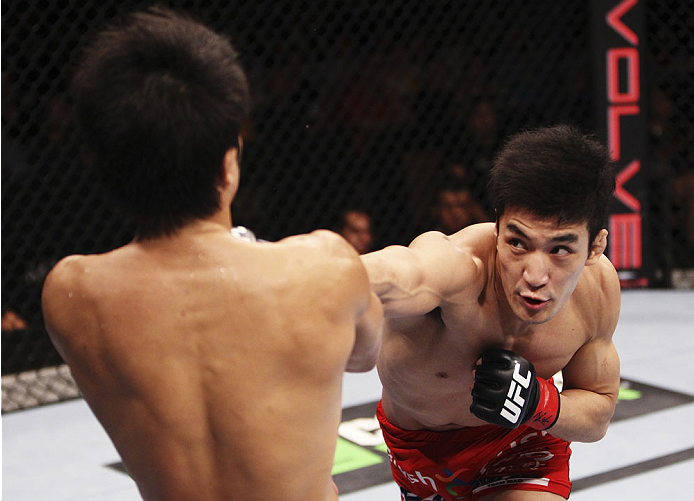 SINGAPORE - JANUARY 04: Kang Kyung Ho goes for a punch on Shunichi Shimizu in their bantamweight bout during the UFC Fight Night event at the Marina Bay Sands Resort on January 4, 2014 in Singapore. (Photo by Mitch Viquez/Zuffa LLC/Zuffa LLC via Getty Ima