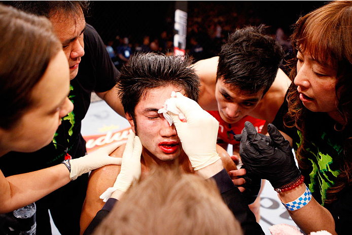 SINGAPORE - JANUARY 04:  Shunichi Shimizu is looked over after his loss to Kang Kyung Ho in their bantamweight bout during the UFC Fight Night event at the Marina Bay Sands Resort on January 4, 2014 in Singapore. (Photo by Mitch Viquez/Zuffa LLC/Zuffa LLC