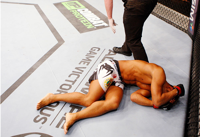SINGAPORE - JANUARY 04:  Kiichi Kunimoto lies on the ground after illegal elbows to the back of the head from his opponent, Luiz Dutra, in their welterweight bout during the UFC Fight Night event at the Marina Bay Sands Resort on January 4, 2014 in Singap