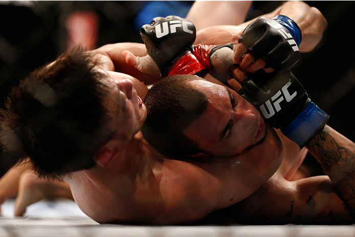 SINGAPORE - JANUARY 04:  (L-R) Tatsuya Kawajiri secures a rear choke submission against Sean Soriano in their featherweight bout during the UFC Fight Night event at the Marina Bay Sands Resort on January 4, 2014 in Singapore. (Photo by Josh Hedges/Zuffa L