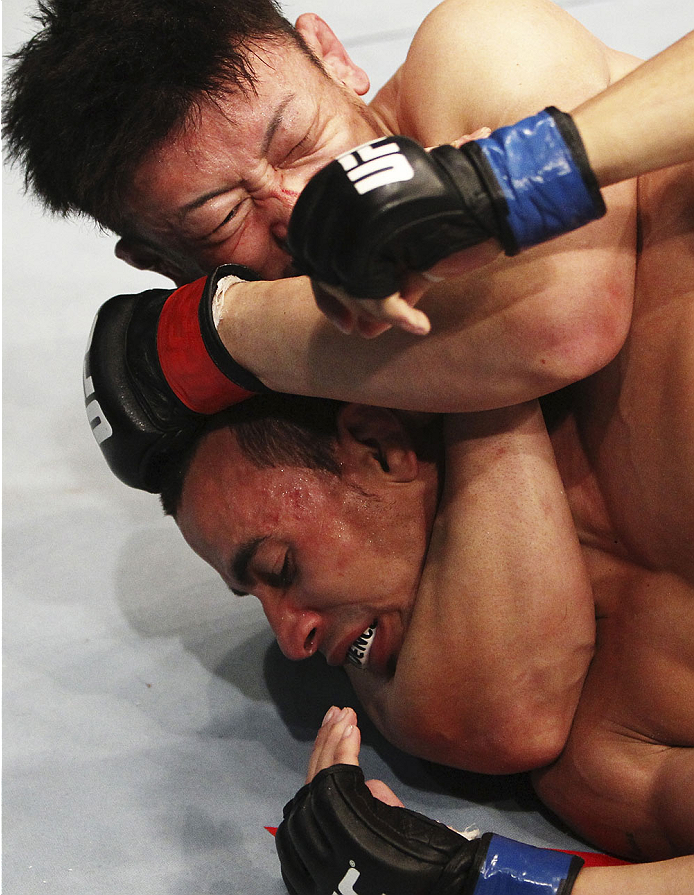 SINGAPORE - JANUARY 04:   Tatsuya Kawajiri  goes for a submission attempt on Sean Soriano in their featherweight bout during the UFC Fight Night event at the Marina Bay Sands Resort on January 4, 2014 in Singapore. (Photo by Mitch Viquez/Zuffa LLC/Zuffa L
